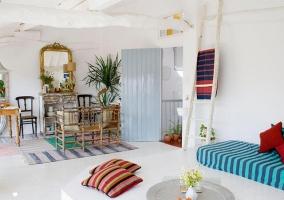 Salón Chill Out decorado con rayas marineras de distintos colores y mesa comedor