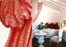 Detalle de la cortina y habitación en tonos blancos y rojos