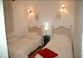 Dormitorio doble con colchas y cabecero de madera junto a la ventana