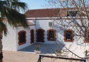 Acceso principal con fachada en color blanco y palmeras delante
