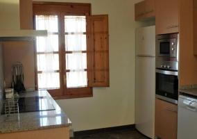 Cocina con armarios de madera y vitro en la encimera