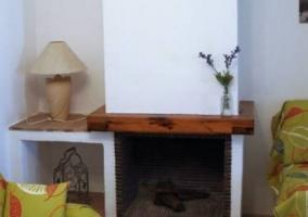 Sala de estar con la chimenea y sillones frente a ella
