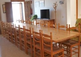 Sala de estar y comedor con mesa muy amplia y sillas