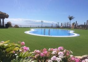 Acceso con zonas verdes y piscina en el centro