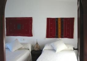 Dormitorio de matrimonio con colchas en color crudo