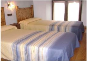 Habitación con cama matrimonial y pared roja de la casa rural