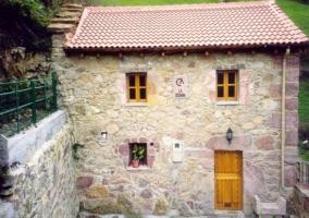 Acceso con fachada de piedra dividida en 2 plantas