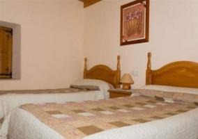 Dormitorio doble con cabecero de madera y cuadro