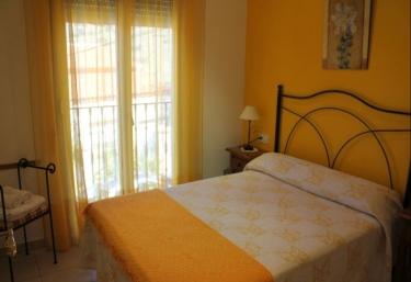 Cama con pared y cortinas amarillas en el dormitorio de la casa rural