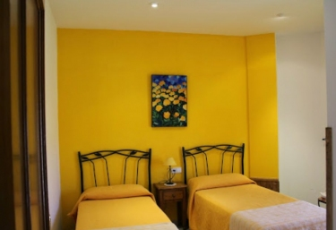 Cuadro azul en habitación doble con decoración en tonos amarillos