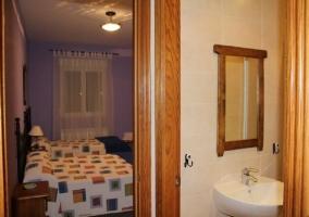 Dormitorio con dos camas y baño propio en la casa rural