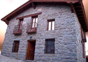 Acceso a la casa con su fachada en piedra de la zona