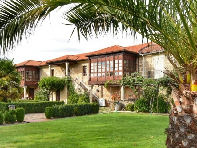 Acceso principal al alojamiento con jardines y palmeras