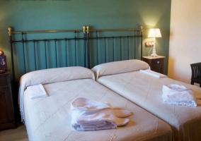 Dormitorio doble con las toallas sobre las colchas