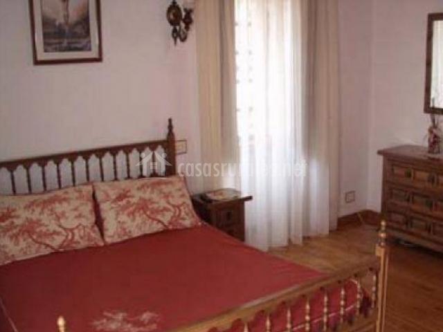 Dormitorio de matrimonio con colcha en color burdeos y cabecero de madera