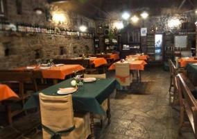 Comedor con paredes de piedra y mesas de madera