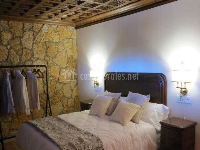 Dormitorio con cama amplia y techos de madera