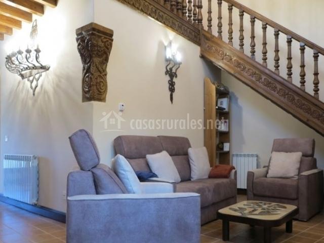 Sala de estar con sillones y escalera en un lado