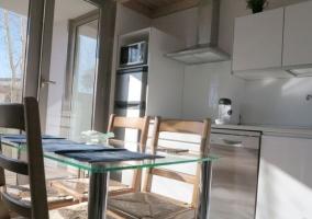 Cocina comunicada con el comedor y su mesa de cristal