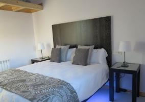 Dormitorio de matrimonio con manta y mesillas
