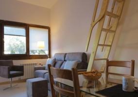 Sala de estar con mesa de madera y sillones junto a la escalera