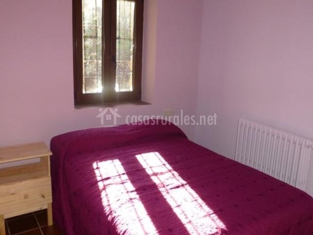Dormitorio con cama amplia bajo la ventana