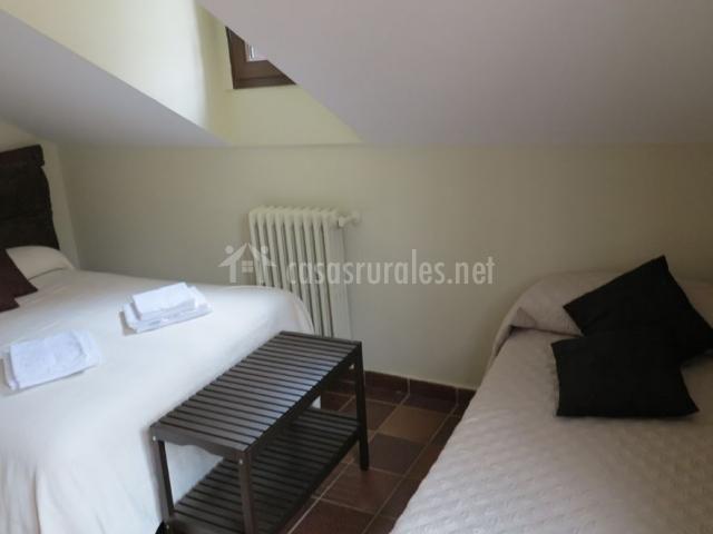 Dormitorio de matrimonio abuhardillado y una cama adicional