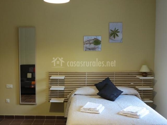 Dormitorio de matrimonio con muebles de madera y colchas en tonos beige