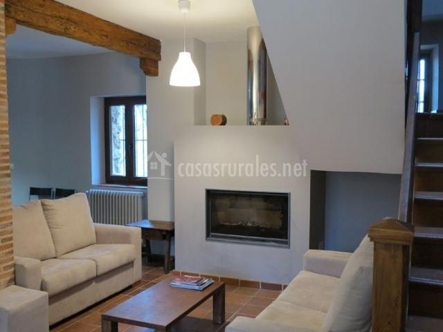 Sala de estar con chimenea y mesa entre los sillones