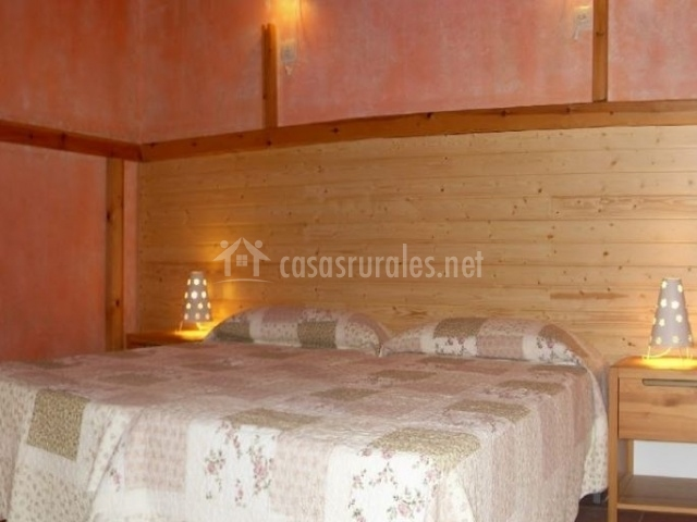 Dormitorio doble con la pared de madera