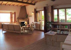 Sala de estar con sillones y una chimenea en la esquina
