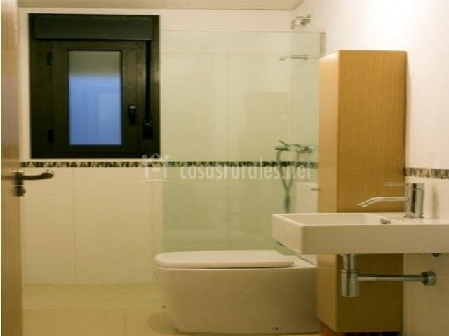 Baño con ducha y mueble de madera