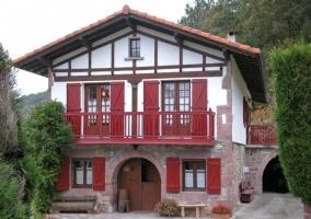 Acceso principal a la casa con puerta grande de madera