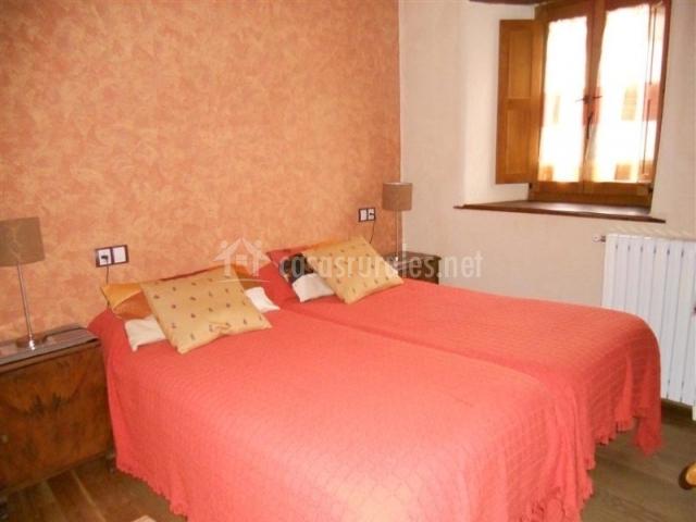 Dormitorio doble con dos camas y ventana