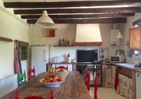 Cocina con mesa de madera y unas sillas de colores