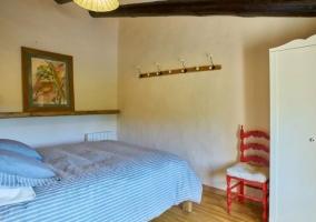 Dormitorio con colcha de rayas y armario en blanco