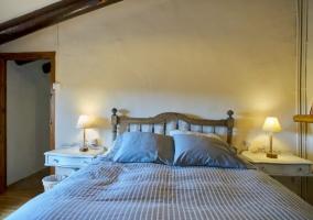 Dormitorio de matrimonio con vigas en madera y mesillas