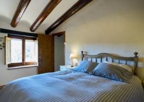Dormitorio de matrimonio con vigas en madera y ventanas