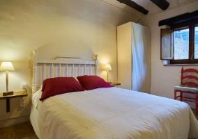 Dormitorio de matrimonio en blanco y cojines rojos