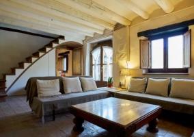 Sala de estar luminosa con sillones y mesa grande