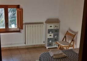 Dormitorio amplio con colchas en gris y blanco