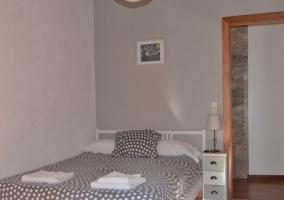 Dormitorio con cama amplia decorada en blanco y gris