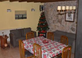 Sala de estar con mesa de madera y paredes de piedra