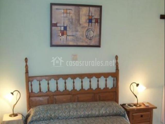 Dormitorio de matrimonio con cuadro sobre el cabecero en madera