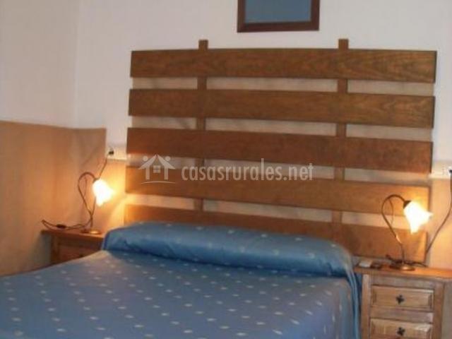 Dormitorio de matrimonio con original cabecero y colcha azul