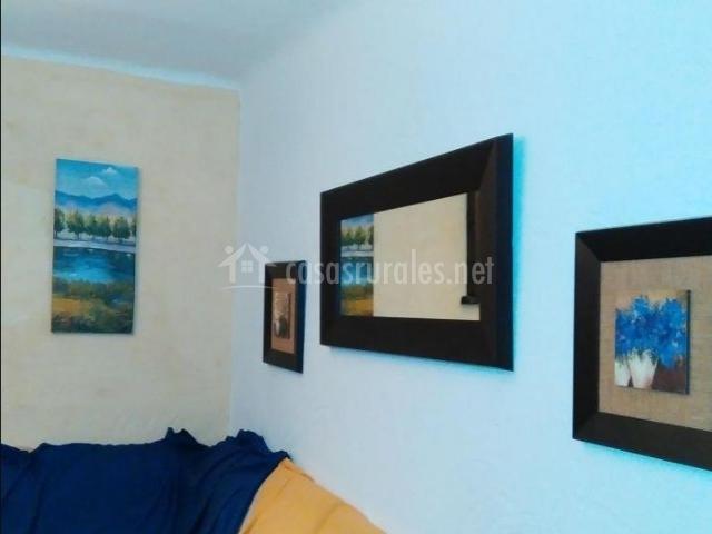 Sala de estar con cuadros y espejo en la pared