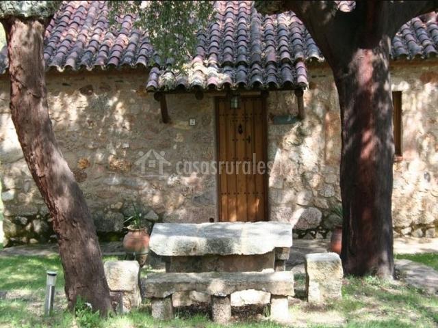 Acceso a la casa con mesa y banco de piedra