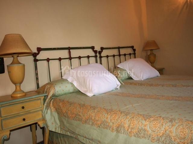 Dormitorio doble con colchas estampadas y cojines