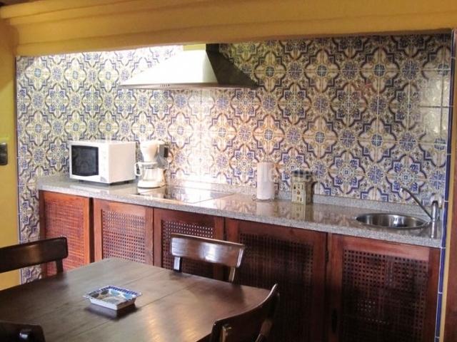 Cocina comedor con mesa de madera y azulejos