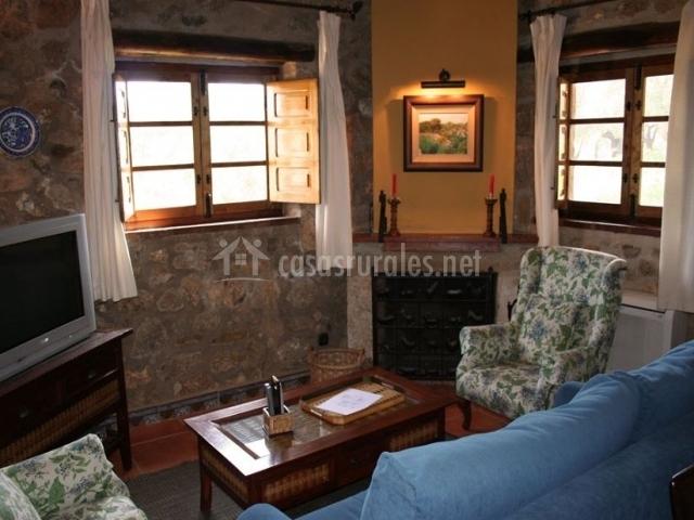 Sala de estar con chimenea decorada con un cuadro iluminado